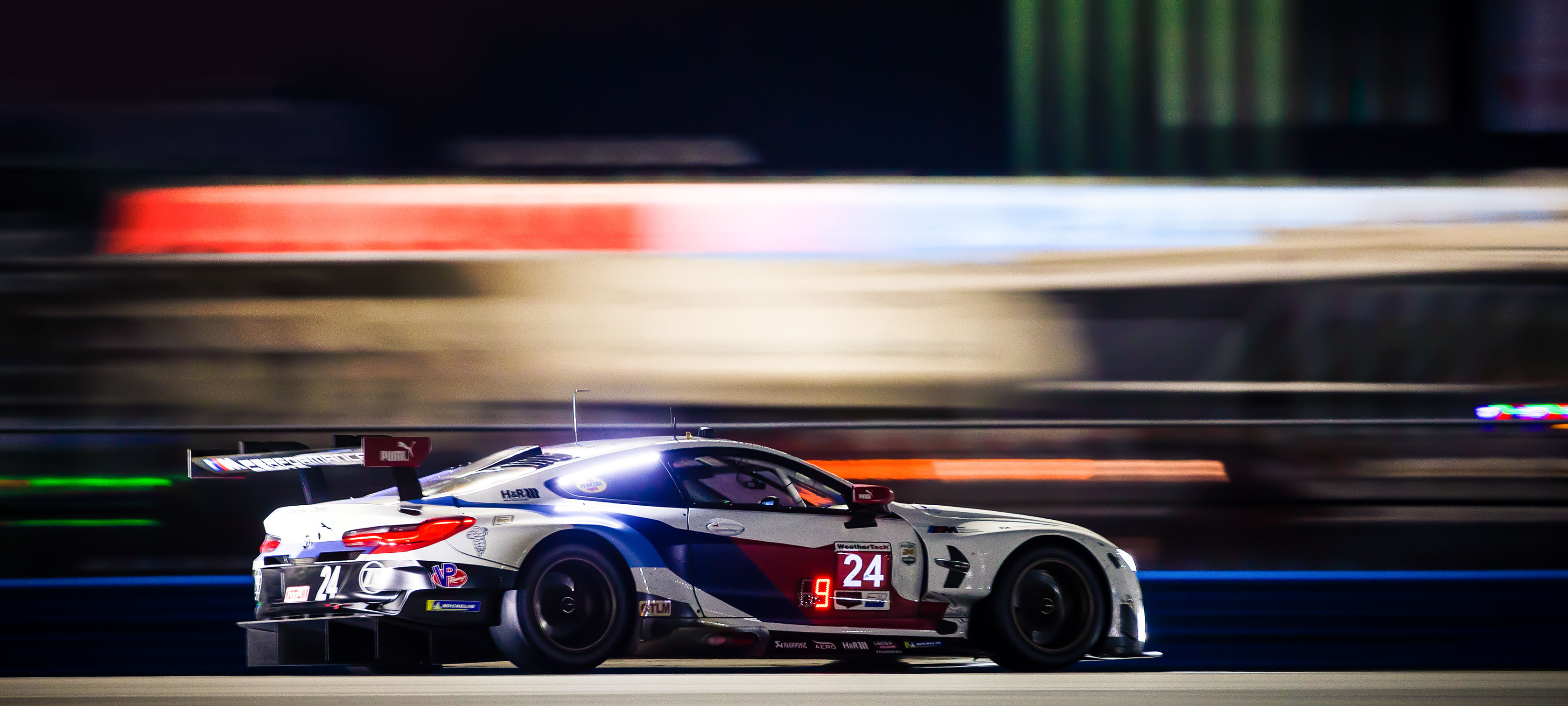 A BMW Motorsport race car is driving through the night.